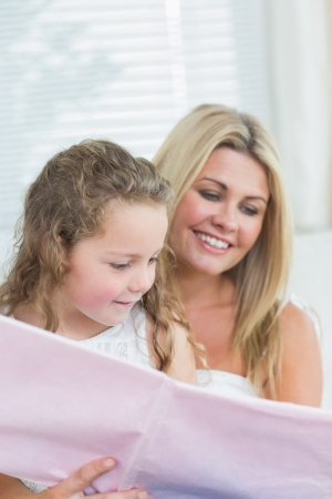 Smiling daughter and mother reading book together in living room photo