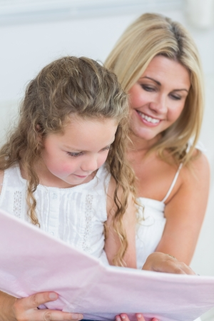 Smiling mother and daughter reading storybook together photo