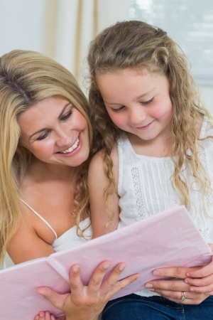 Smiling daughter and mother reading storybook together photo