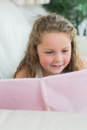Smiling girl lying on the sofa reading a book photo