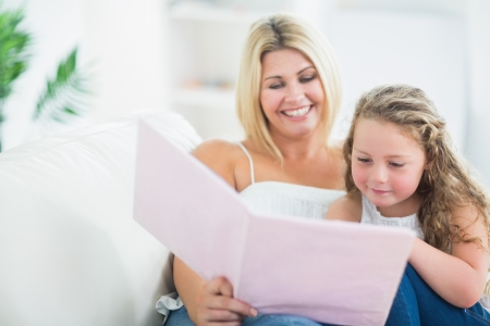 Mother with her daughter reading book on the sofa photo