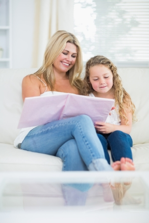 Smiling mother and daughter while reading book on couch photo