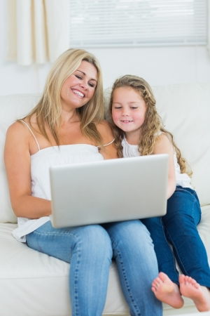 Smiling daughter and mother using notebook photo