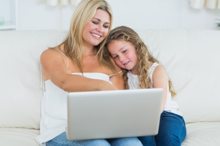 Smiling mother showing something to her daughter on laptop photo