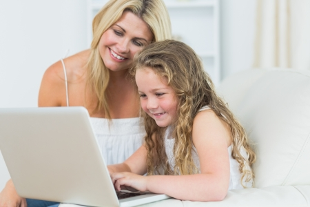 Smiling daughter and mother working with notebook photo