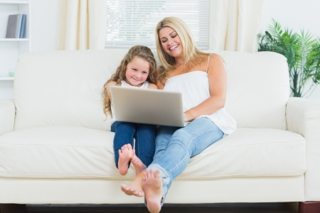 Smiling daughter and mother resting on the sofa with laptop Stock Photo - 16075964