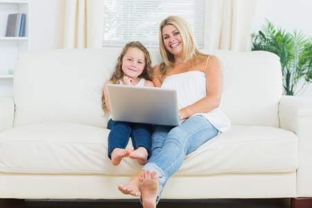Smiling daughter and mother relaxing on the sofa with notebook while they are looking into the camera photo