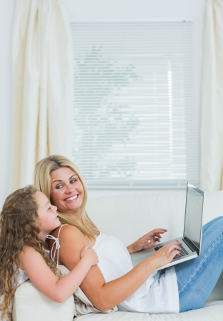 Smiling mother using notebook while looking at her daughter photo