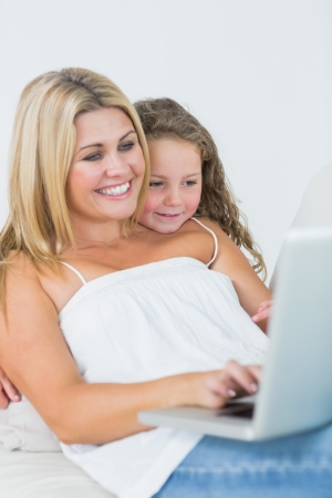 Smiling mother using laptop with her daughter leaning on her shoulder Stock Photo - 16075780