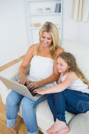 Smiling daughter and mother relaxing on the couch with notebook photo