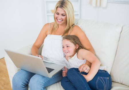 Laughing mother and daughter using notebook during resting on sofa photo