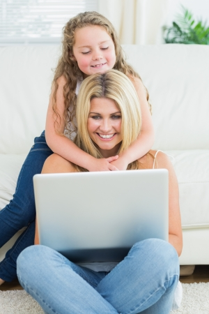 Mother using notebook while sitting on the floor when her daughter hugging her  photo
