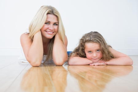 Laughing mother and her daughter resting on the floor photo