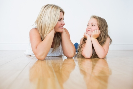 lying on floor: Resting mother and daughter on the floor while they looking at each other Stock Photo