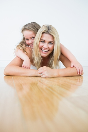 Laughing mother and daughter resting on the floor  photo