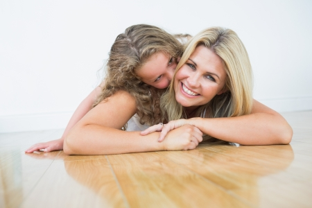 Laughing mother laying with her daughter on the floor photo