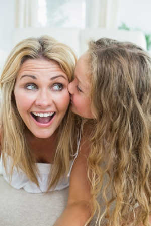 Daughter kissing her mother on the cheek Stock Photo - 16076653
