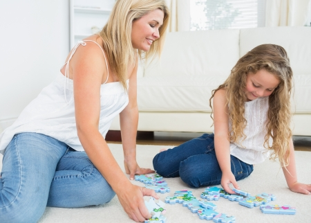 Mother and daughter doing a jigsaw puzzle on the floor photo