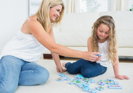 Daughter and mother doing a jigsaw puzzle on the floor photo