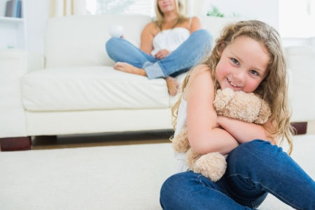 Daughter hugging her teddy bear while her mother is resting on the sofa photo
