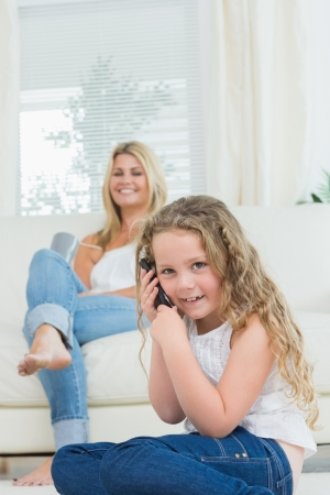 Daughter using mobile phone while her mother laughing on the sofa Stock Photo - 16076384