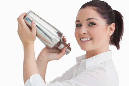 tied hair: Donna sorridente miscelare un cocktail in uno shaker Archivio Fotografico