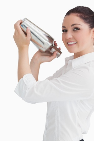 Smiling woman using cocktail shaker photo
