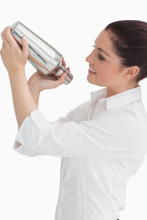 Smiling woman using cocktail shaker while looking at it photo