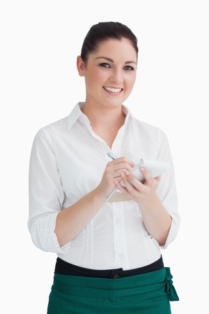noting: Smiling waitress writing an order down on white background