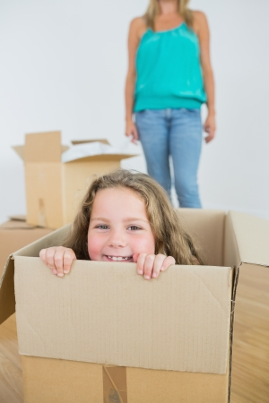 Laughng girl in moving box with mother standing behind Stock Photo - 16076213