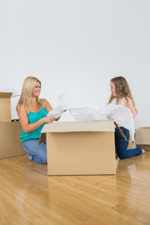 Smiling mother and daughter unpacking and laughing together Stock Photo - 16075903