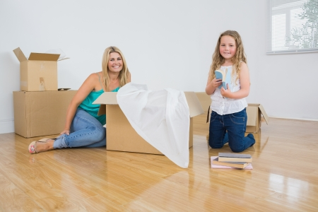 Smiling mother and daughter unpacking boxes photo
