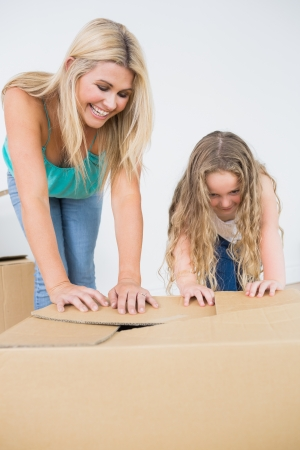 Mother and daughter laughing and closing moving boxes photo