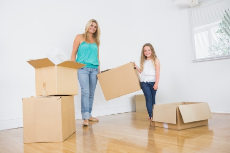 Mother and daughter carrying moving boxes in empty living room photo