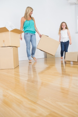 Mother and daughter holding a moving box together in empty living room photo