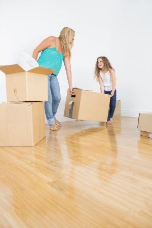 Mother and daughter lifitng moving boxes together in empty sitting room photo