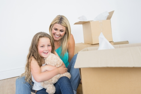 Child holding a teddy bear near her mother in empty living room photo