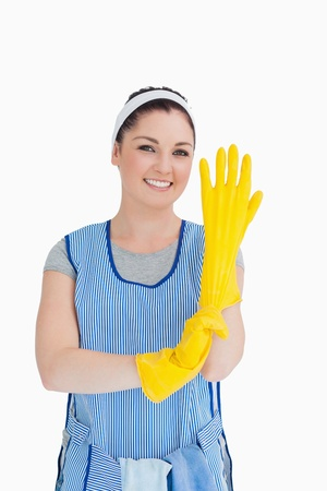 Cleaner woman putting on yellow gloves in the white background photo