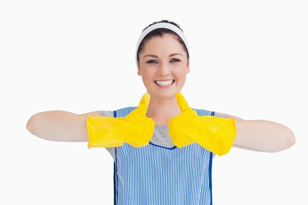 Cleaner woman thumbs up with yellow gloves on the white background photo
