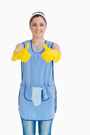 Cleaning woman giving thumbs up with yellow gloves on white background photo