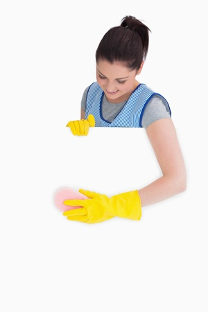 Smiling maid washing with a sponge on the white background photo