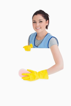 Cheerful maid washing with a sponge on the white background photo