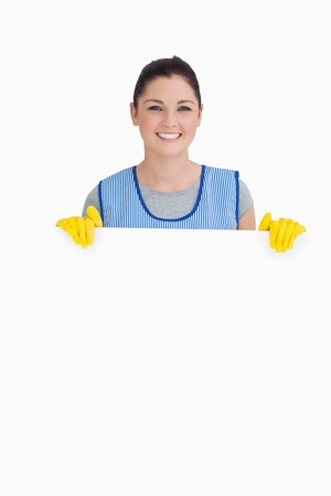 Cleaning woman showing a white panel on the white background  photo