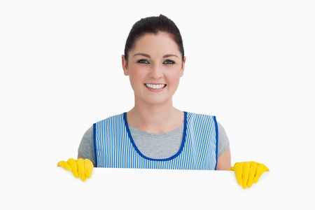 Smiling cleaning woman showing a white panel on the white background  photo