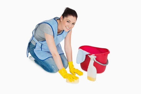 Smiling cleaning woman washing the floor on white background photo