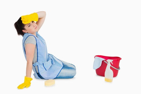 Exhausted woman cleaning the floor on the white background photo