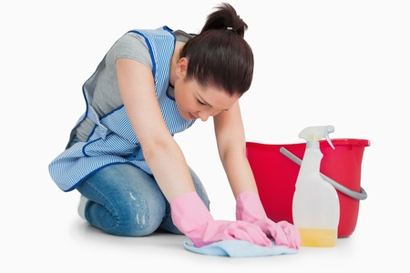 Serious cleaning woman wiping up the floor on the white background photo