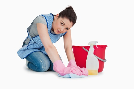 Exhausted cleaning woman wiping up the floor on the white background photo