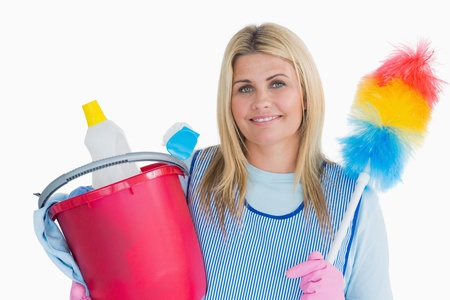 Smiling cleaner woman holding a bucket and feather duster in the white background photo