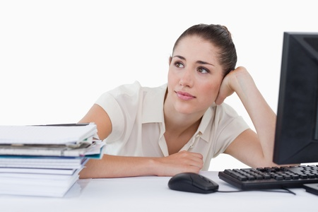Dreaming businesswoman leaning on her desk against a white background photo